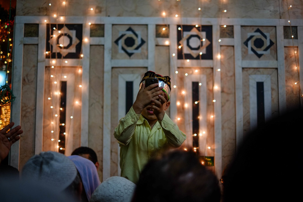 A child tries to to photograph the tomb of Sayeda Zenab amidst the crowds of pilgrims.