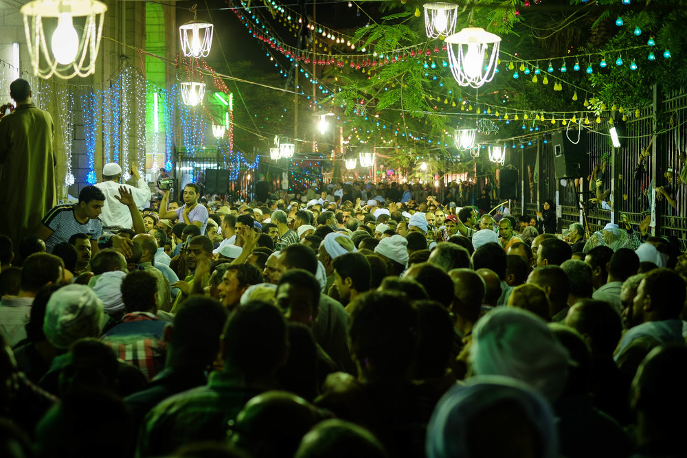 Thousands pack the area outside of the mosque, where impromptu dancing and music begin to alleviate the wait to enter.