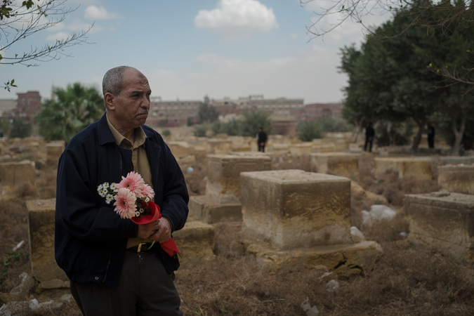 With police securing the area, a man holds a bouquet of flowers to be placed on the grave for Nadia Haroun.