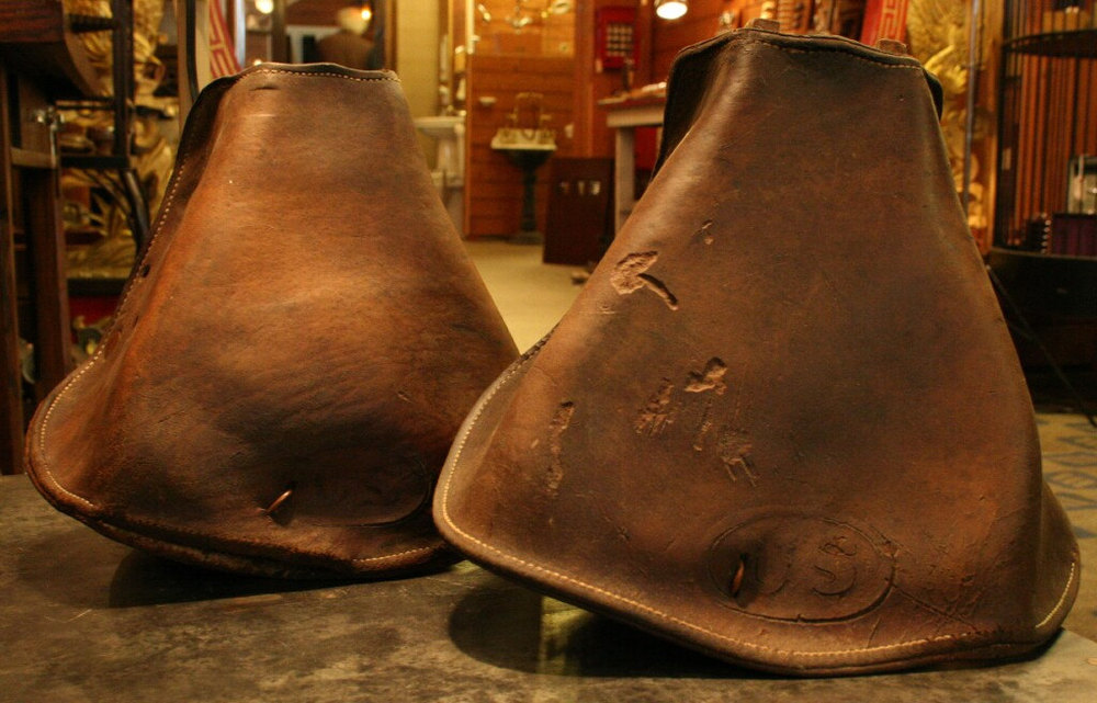 "Original, circa 1910 leather hooded stirrups used by the US Army Cavalry. Each stirrup has US embossed within an oval on the front. These are made of leather and wood and were used on cavalry model McClellan saddles.  Measurements are approximately 8 3/4"" tall x 9 1/2"" wide and 5 3/4"" deep. $95"