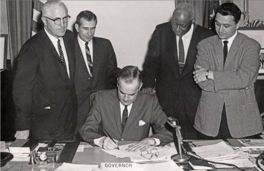 Gov. Matthew Welsh signs the 1963 Indiana Civil Rights Bill (S. 131) witnessed by sponsors (standing L-R) Marshall Kizer, Robert Rock, Robert Brokenburr, and L. Keith Bulen. Photo credit: Indiana Historical Society Digital Image Collections.