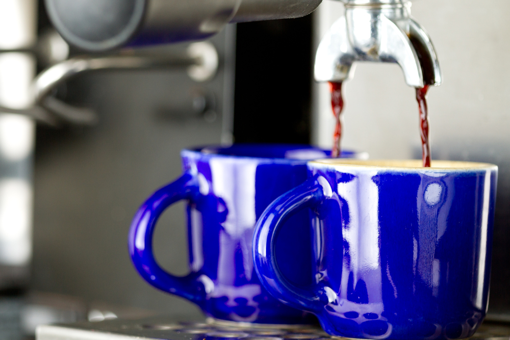 Professional food photo of coffee being brewing from a expresso machine on blue cups. Commercial photography