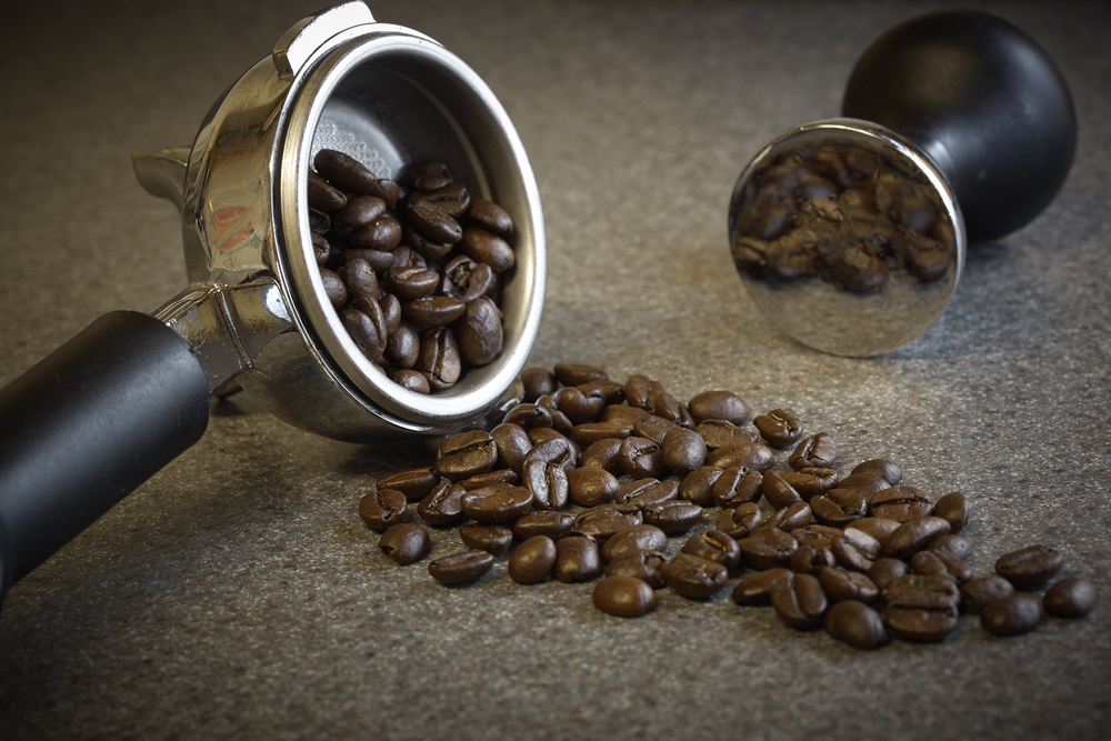 Professional food photo of coffee beans spilling from a expresso machine portafilter. Commercial photography