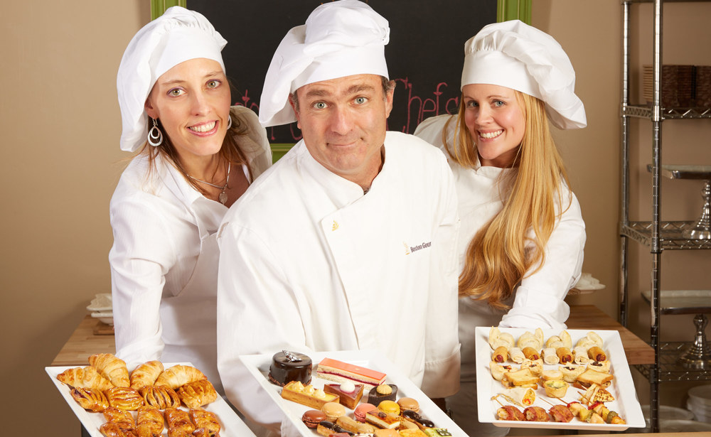 Professional photo for a business holiday card. Two women and a man dressed with chef clothing showing food on trays.