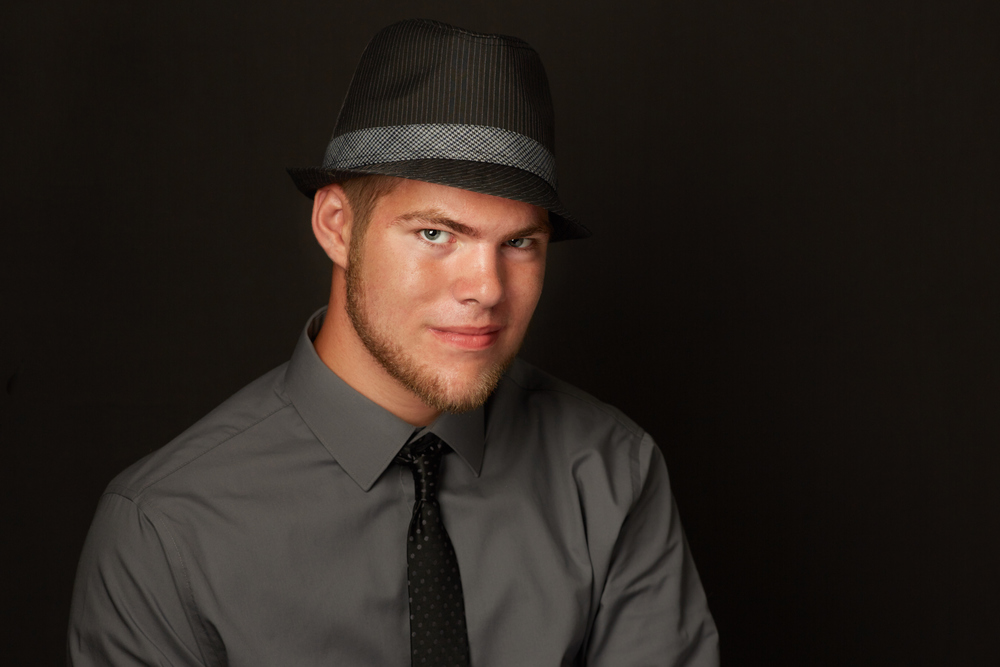 Professional portrait of a young man with a hat in a studio environment with a solid gray background