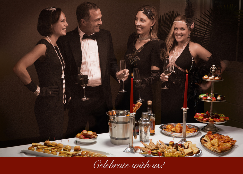 Professional photo for a business holiday card. Three women and a man dressed in 1930's customs around a dinner table with food.