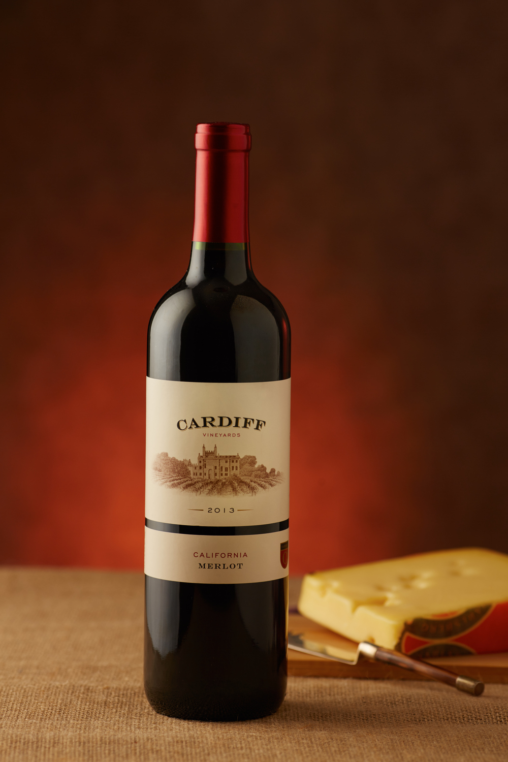 Professional photo of a bottle of Cardiff Merlot red wine on a wood table with Swiss cheese behind the bottle. Photo take in studio with a black background and a red gradient. Commercial photography