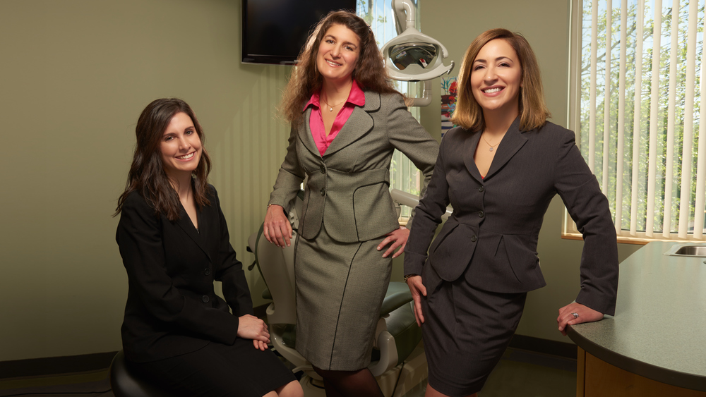 Professional portrait of three dentist women in a dentist office environment.