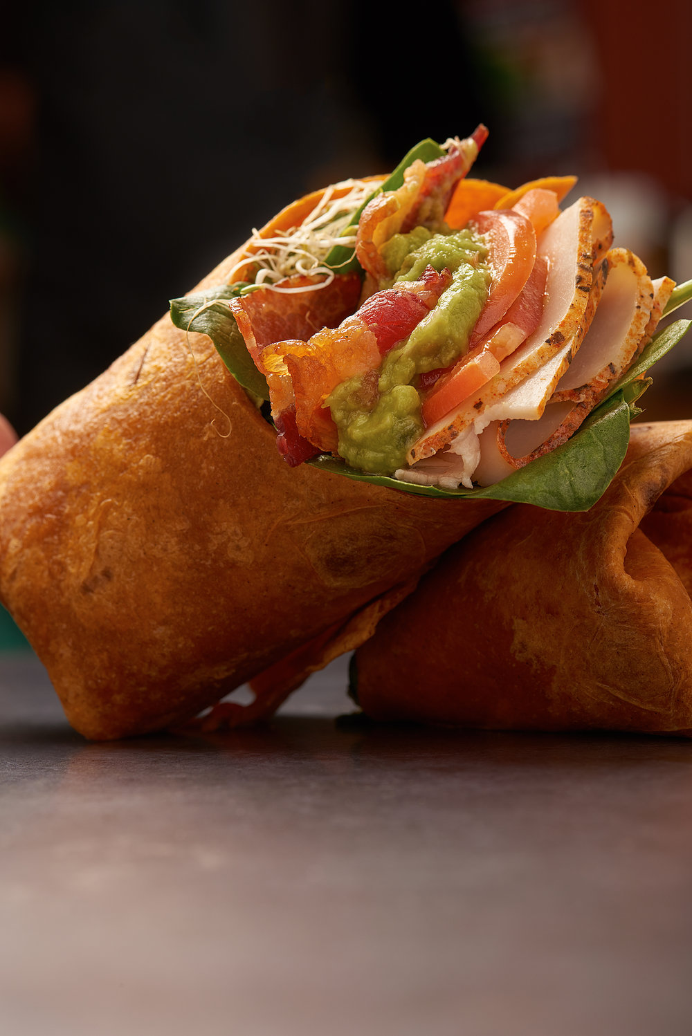 Professional food photo of a wrap made with turkey, tomato, spinach, guacamole and bacon. Commercial photography