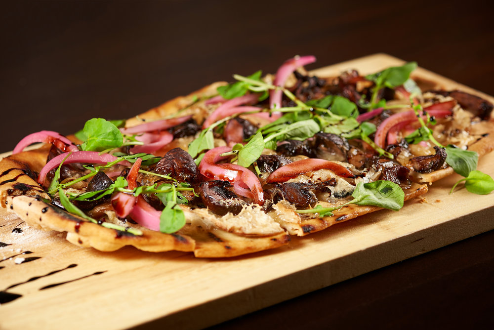 Professional food photo of a wild mushroom pizza flat bread with pickle onions and arugula. Commercial photography