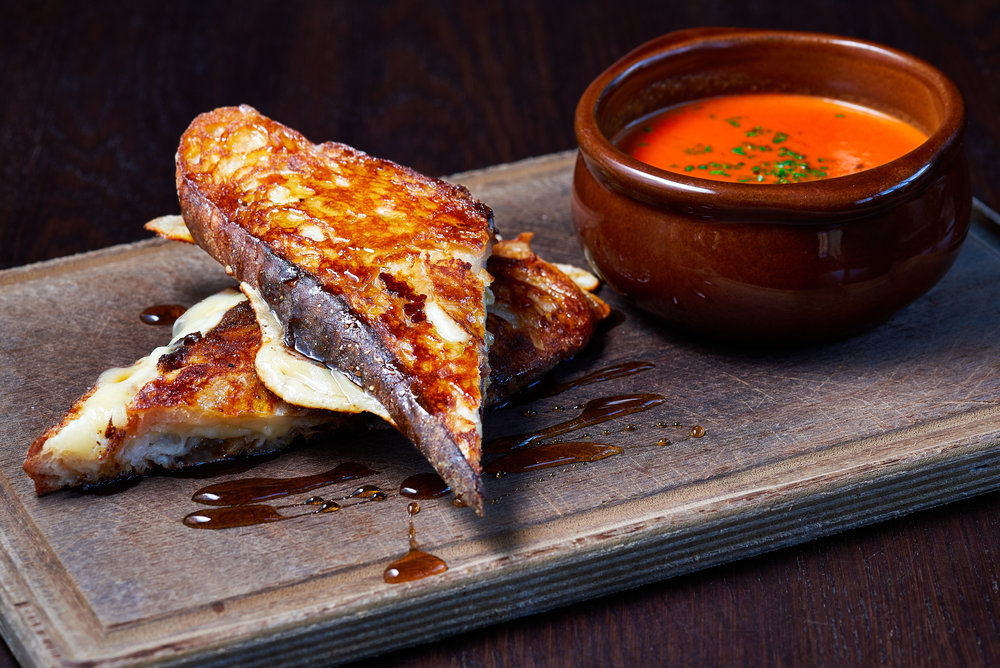 Professional food photo of a grilled cheese sandwich with smoked honey and tomato soup on the side. Commercial photography. Photo taken by Lupa Photography