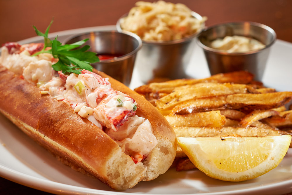 Professional food photo of a lobster roll sandwich with french fries and coleslaw on the side. Commercial photography
