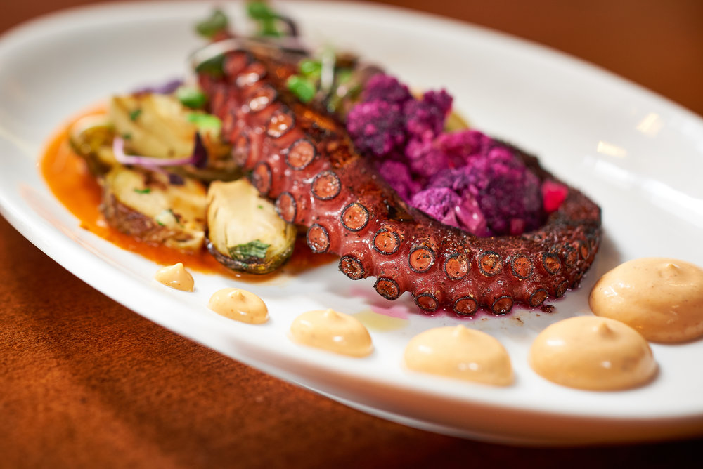 Professional food photo of grilled octopus with brussels sprouts and purple cauliflower. Commercial photography
