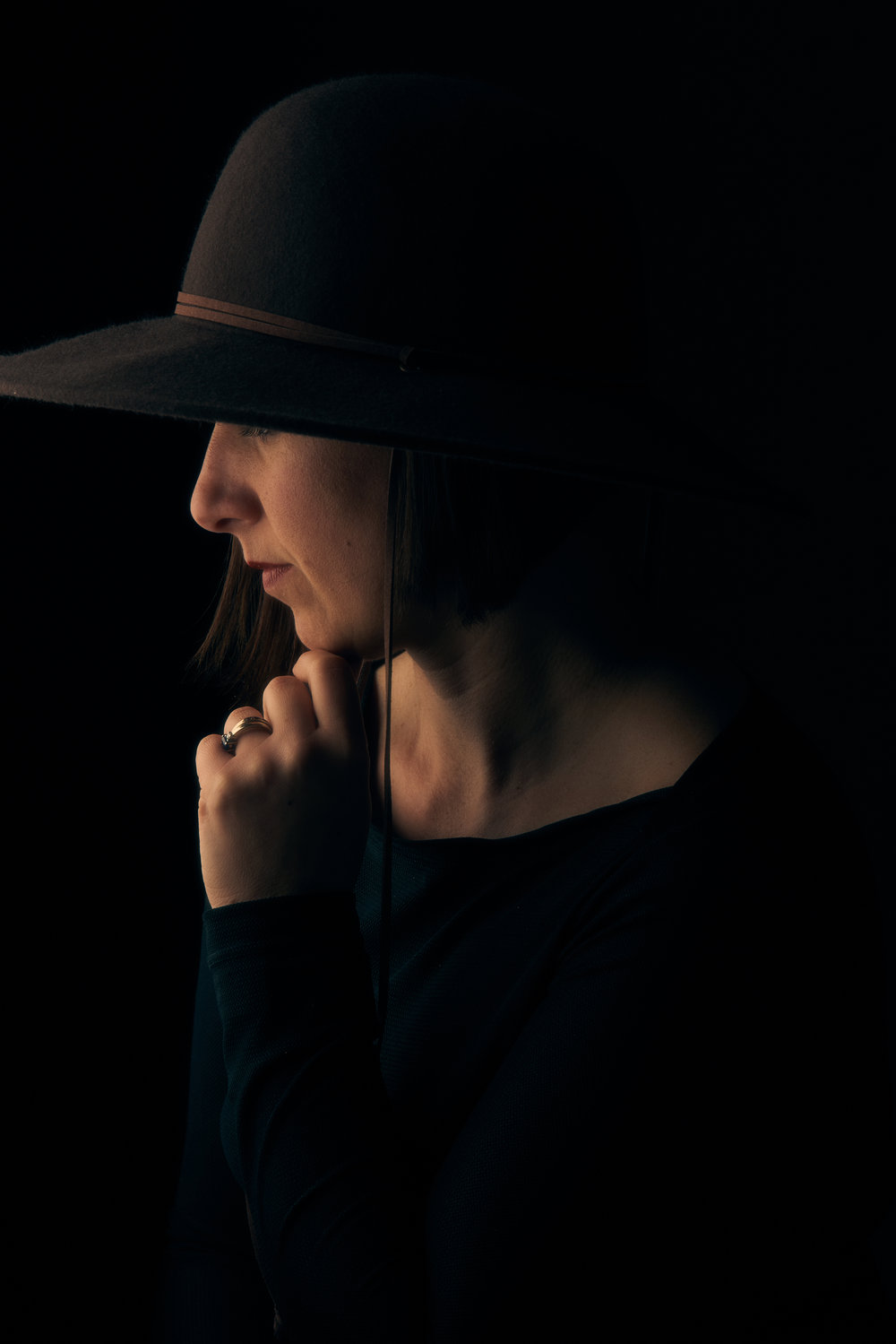 Professional portrait of woman's profile wearing black and with a black hat in a studio environment with a solid black background