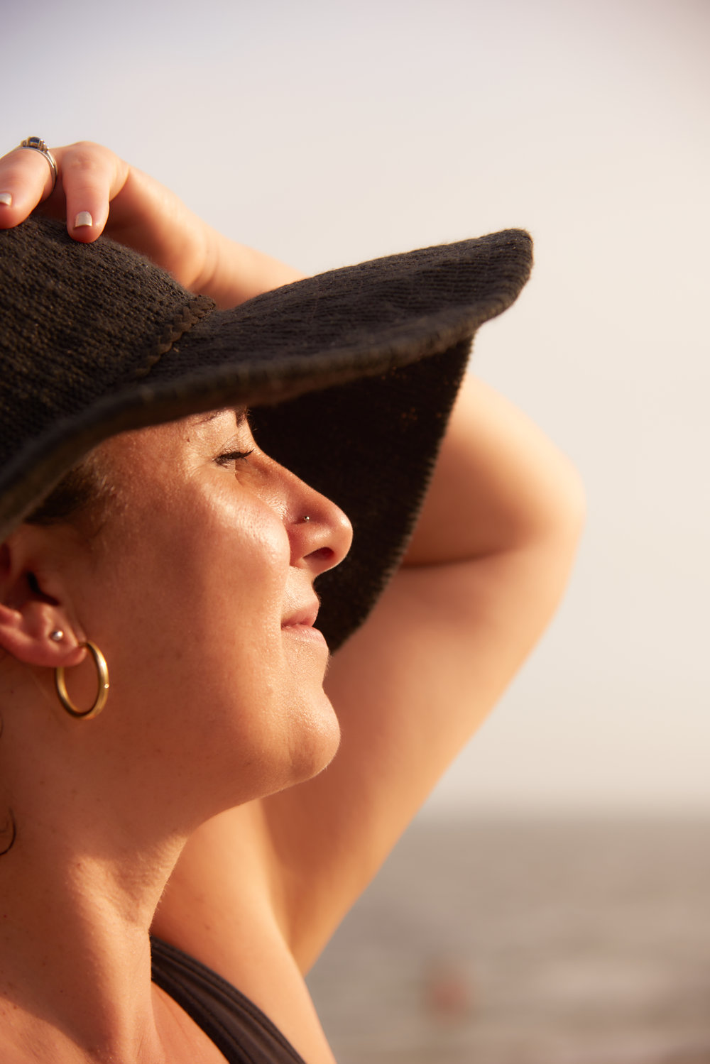 Professional portrait of woman model with a black hat at the beach with the sun on her face.