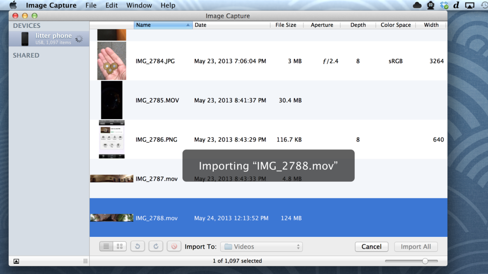 Use the free Image Capture utility or iPhoto to retrieve movies from your phone.