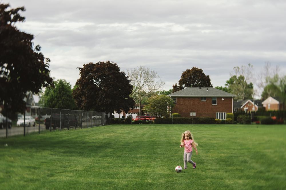 Girl kicks a soccer ball | Francesca Russell Photography & Films | Garden City Family Photographer