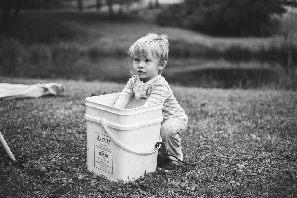 Logan playing in a bucket of pond water.