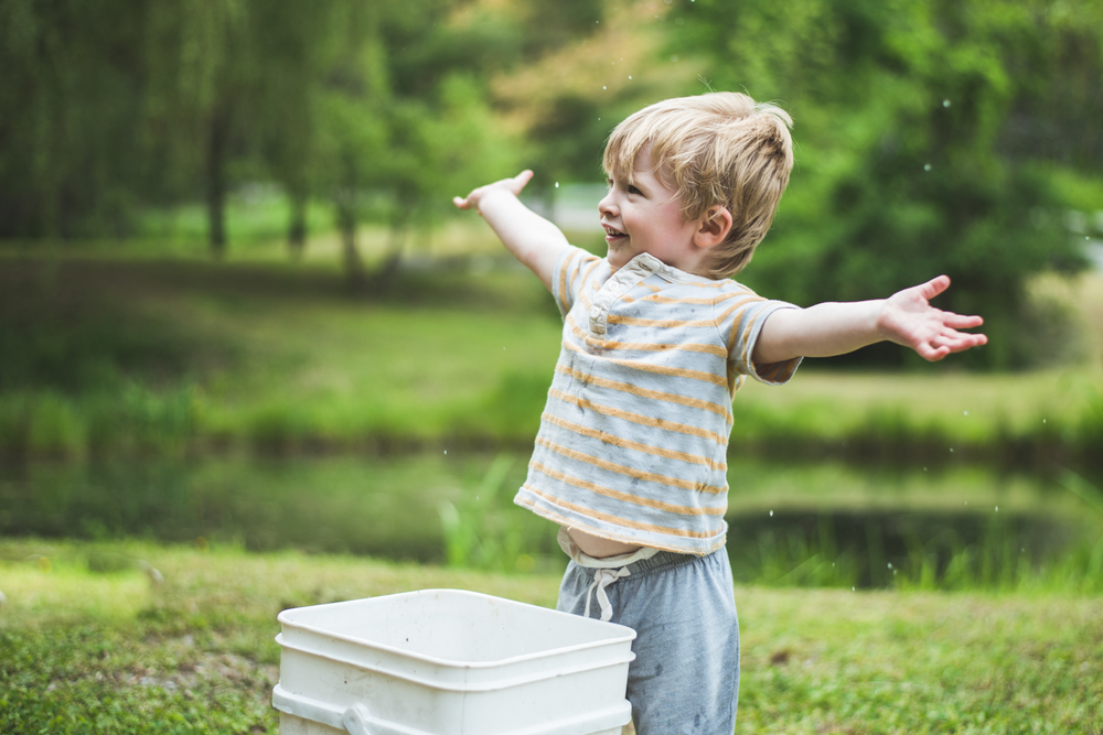 Little boy splashing water from bucket | Francesca Russell Photography | Nassau County Family Photographer