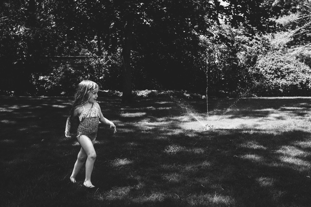 Francesca Russell Photography | Documentary Family Photographer on Long Island | Girl running in sprinkler