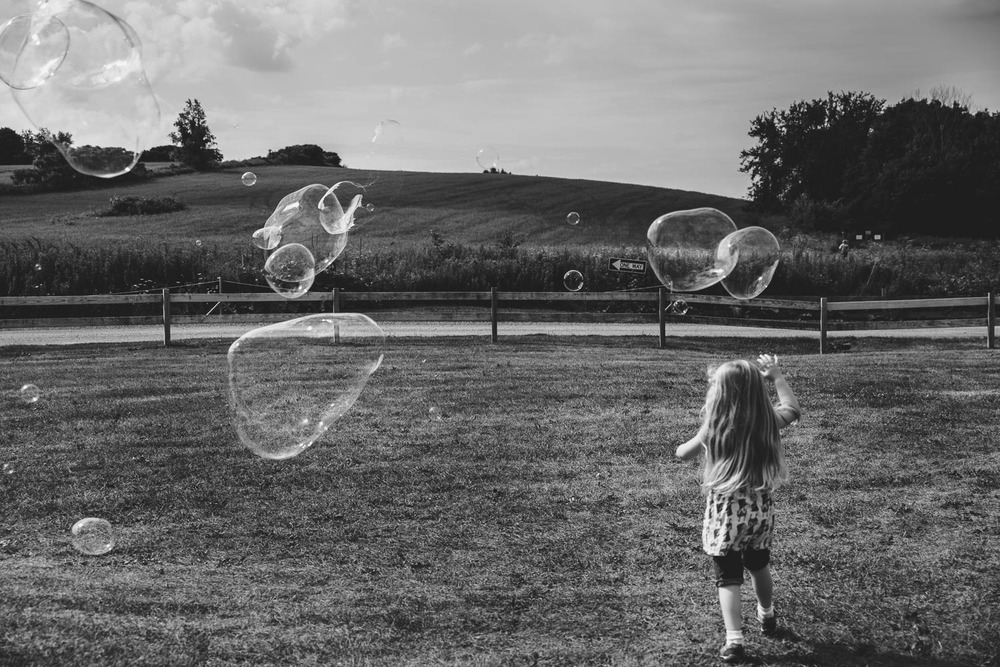 Francesca Russell Photography | Documentary Family Photographer on Long Island | Girl chasing bubbles