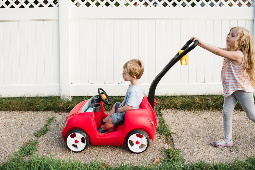 Francesca Russell Photography | Long Island Family Documentary Photography | Lila pushing Logan in his red car