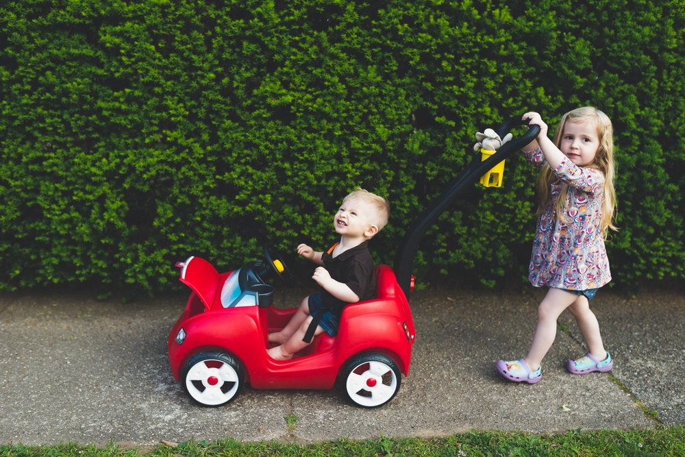 Francesca Russell Photography | Long Island Storytelling Photographer | Lila pushing Logan in his red car