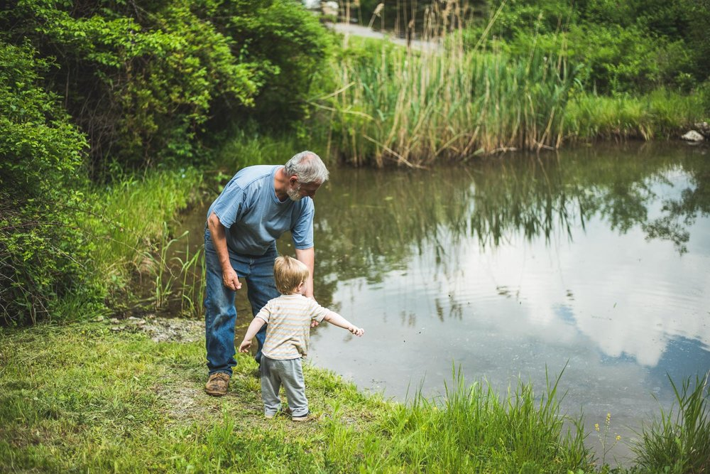 Grandpa showing son how to throw rock in Pond in Copake, New York.