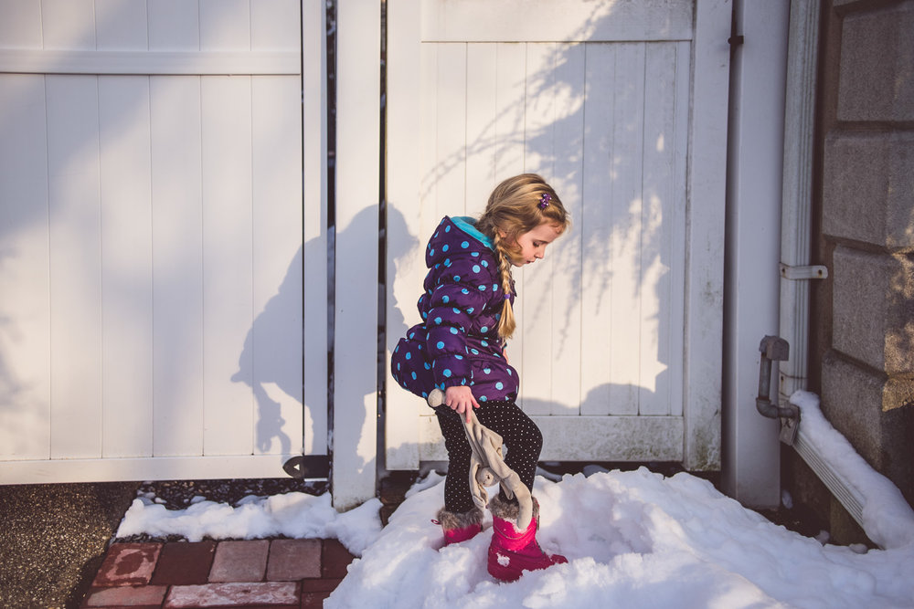 Girl playing on snow in driveway on Long Island.
