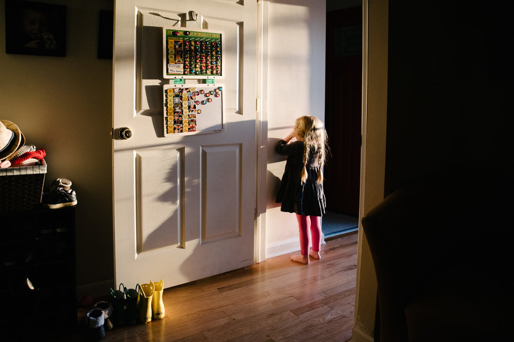 Girl playing hide and seek in hallway at home on Long Island.