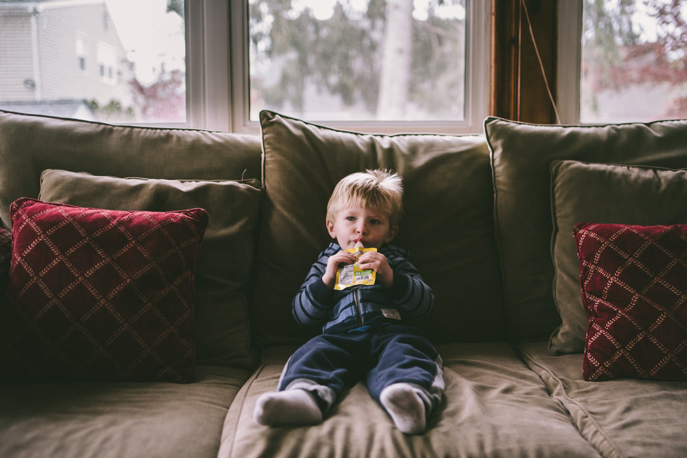 Boy eating a baby food pouch on the sofa
