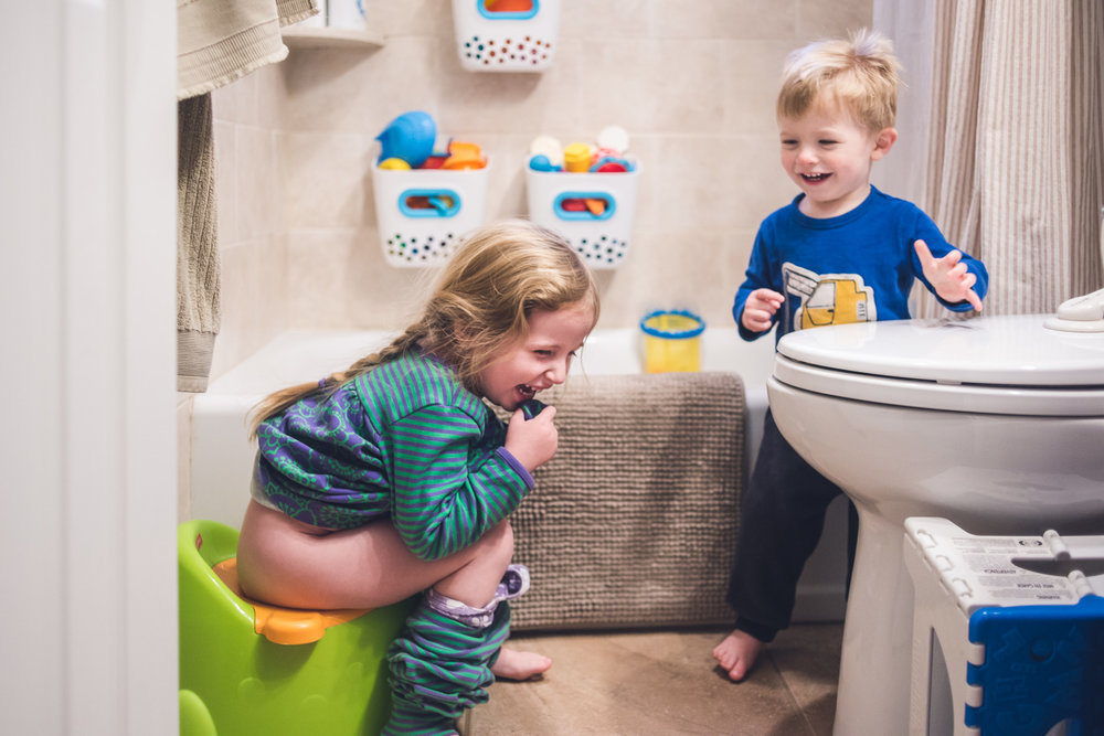 Girl on potty while little brother stands by and laughs.