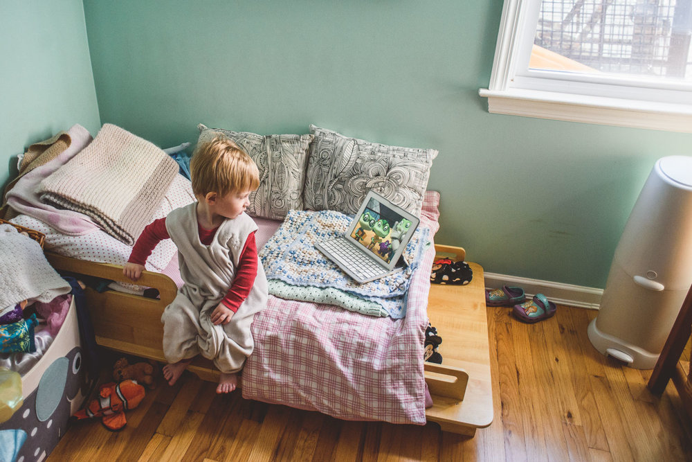 Little boy sitting on a toddler bed watching the iPad.