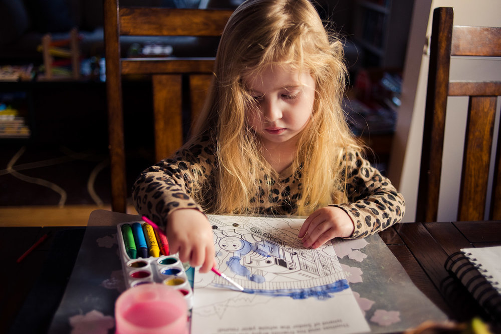 Little girl painting at the kitchen table.
