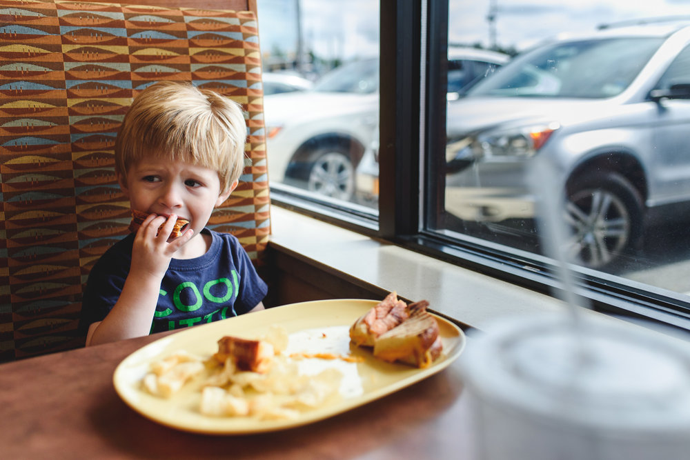 Boy eating a grilled cheese at Panera in Carle Place.