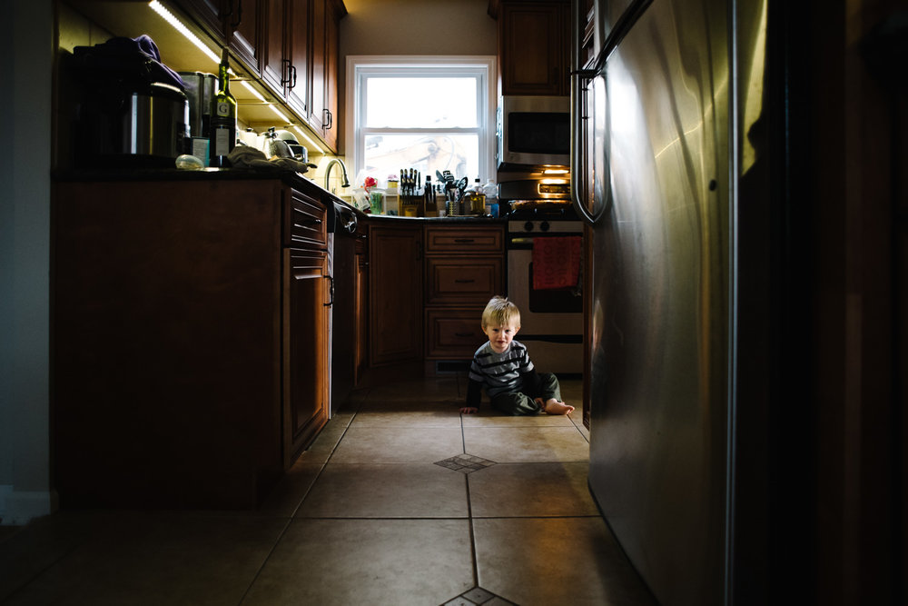 Toddler on floor of kitchen in Garden City South, NY.