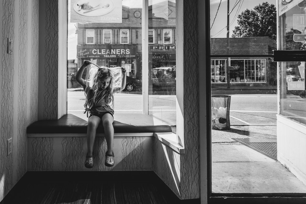 Little girl playing with her hair in the window of Handles, yogurt shop in Garden City.