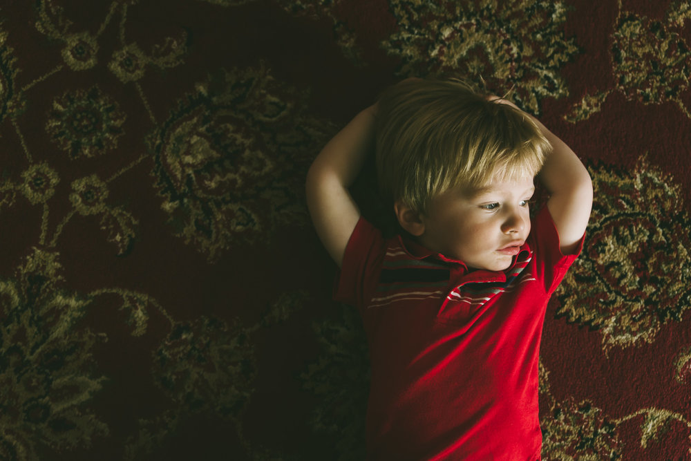 Little boy lying on patterned carpet.