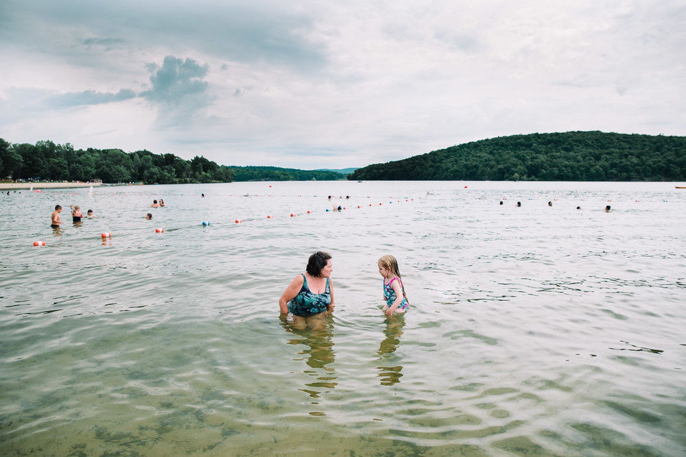 Little girl and grandmother swimming in the lake.