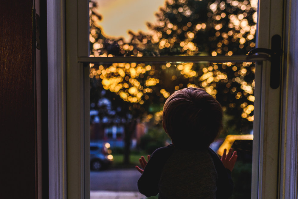 Boy looking out door at sunset.