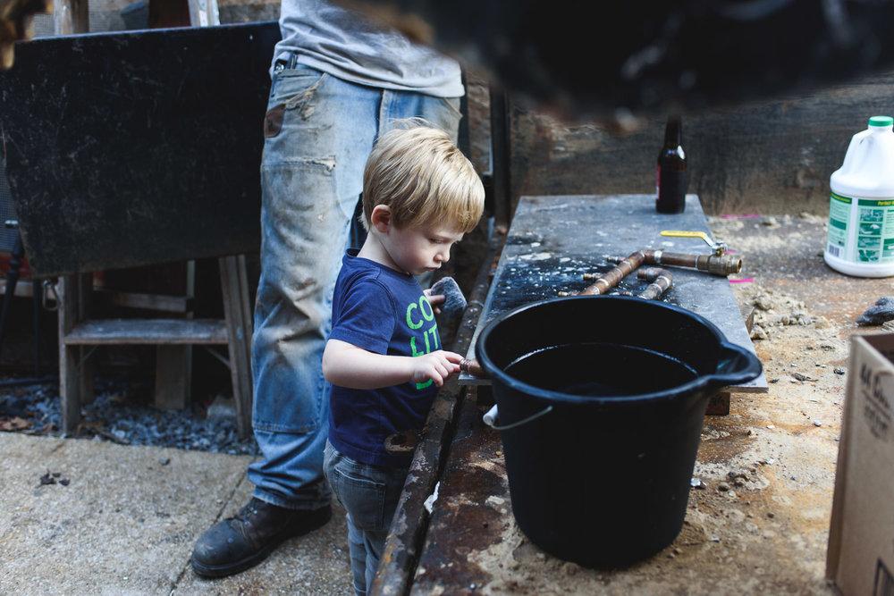 Boy helping dad in the backyard.