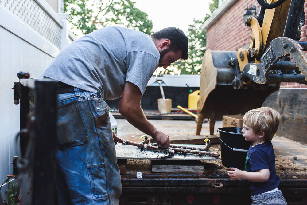 Dad and toddler son working in the driveway.