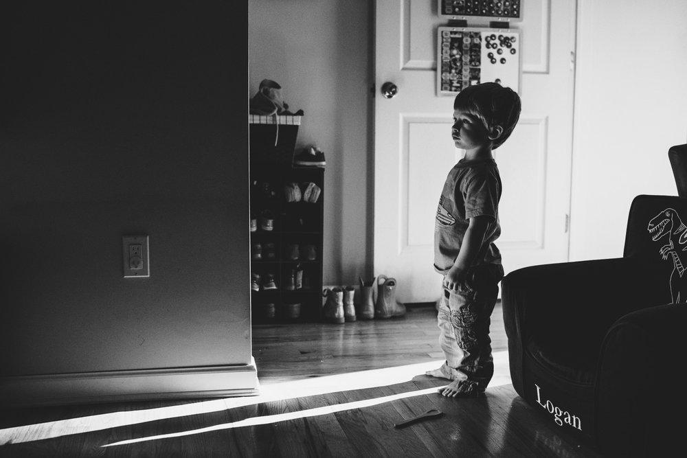 Boy standing in light from doorway.
