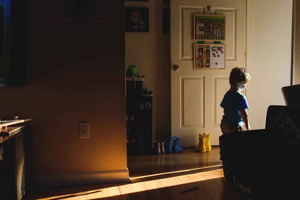 Boy walking toward light of front door.
