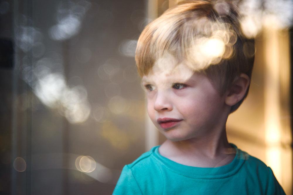 Boy at sunset through the storm door.