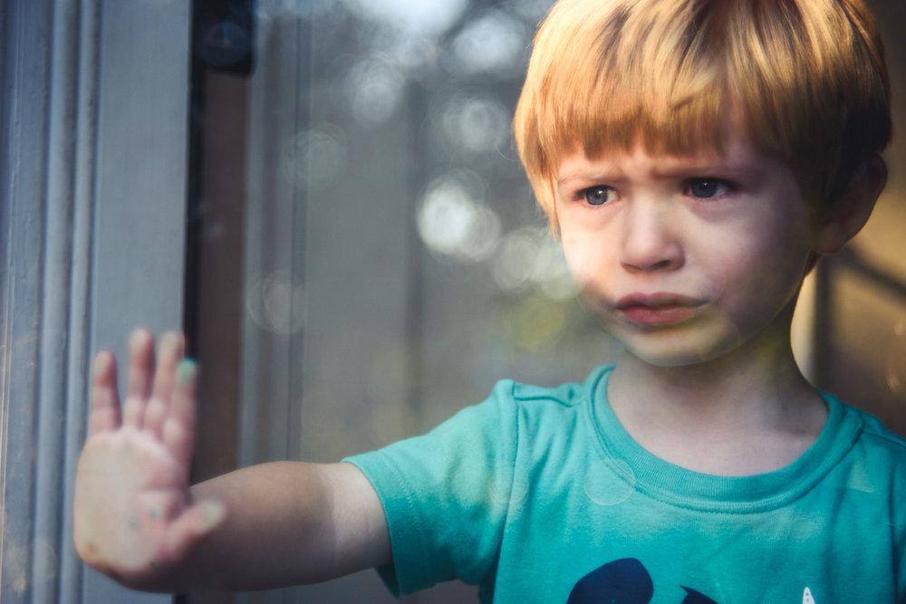 Upset boy pushing on storm door.