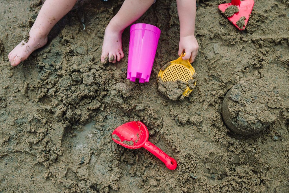 Child playing with sand toys in wet sand.