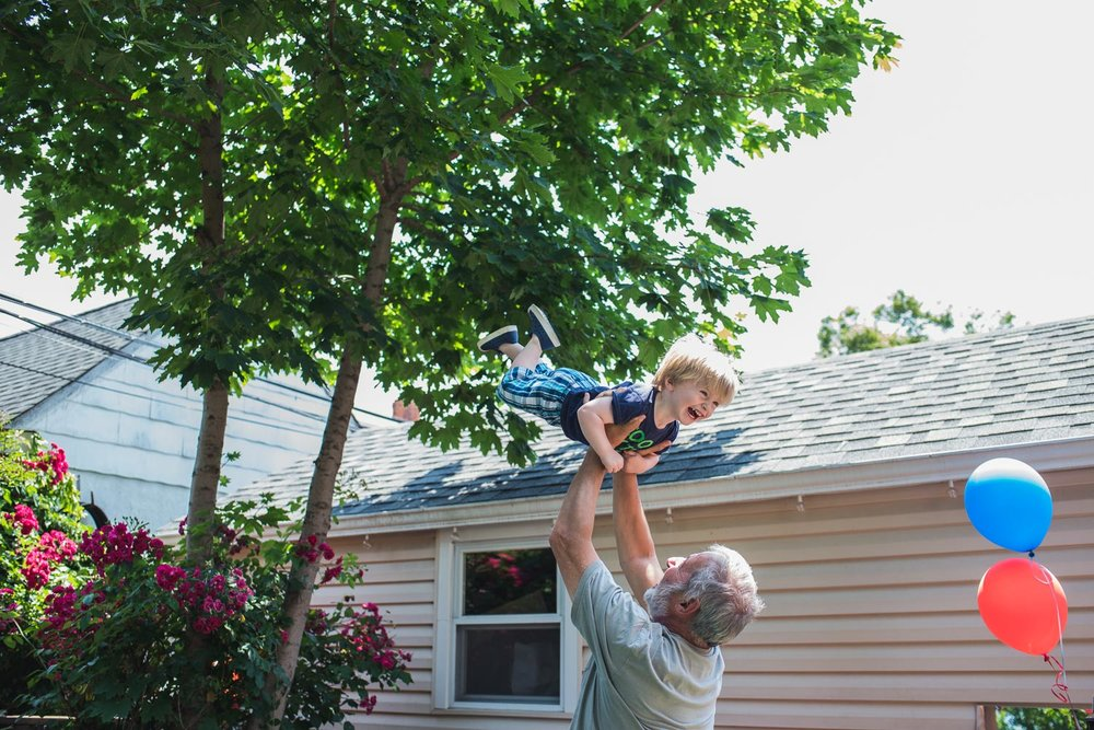 Little boy being thrown in the air by grandfather at birthday party.