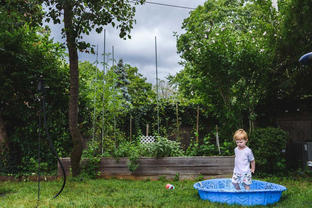 Little boy in backyard kiddie pool as storm clouds roll in.