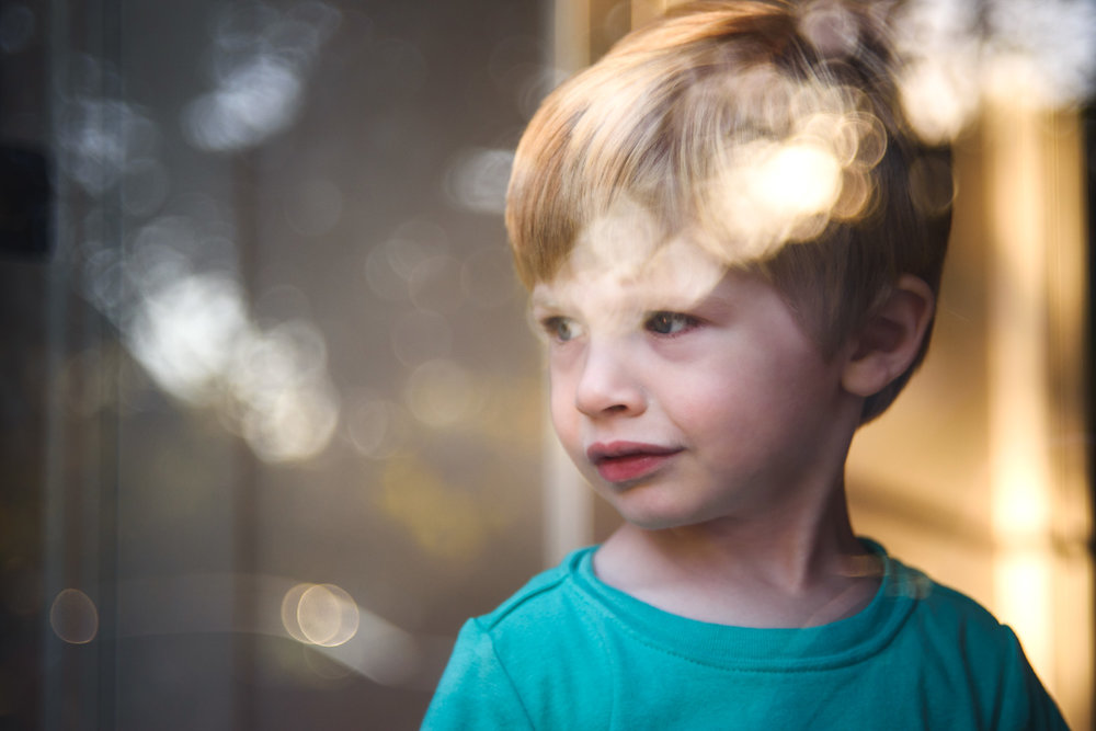Experiments with the Helios lens: Logan at the golden hour, looking out the storm  door.